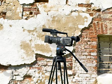 Videocamera near wall stock photo, Single working videocamera against the old wall by Sergej Razvodovskij