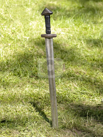 Sword stock photo, Old metal sword in the green grass by Sergej Razvodovskij