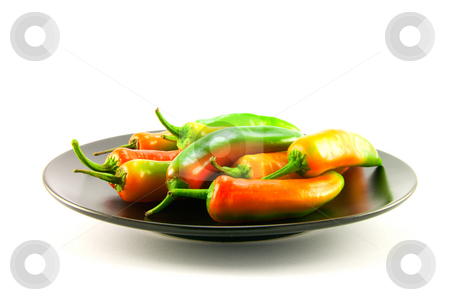 Chillis on a Black Plate stock photo, Red and green chillis on a black plate with clipping path on a white background by Keith Wilson