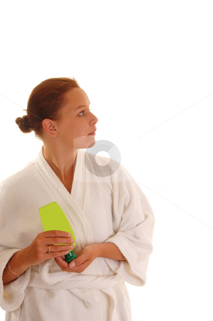 Woman with lotion. stock photo, A young woman in an bad robe putting lotion after the shower on her face, for white background. by Horst Petzold