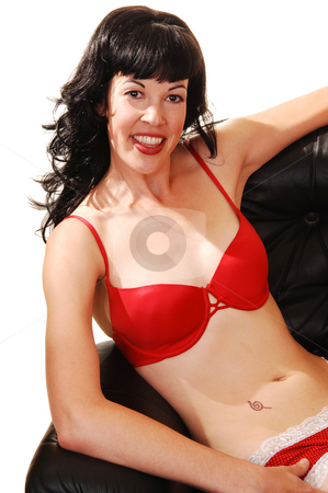 Girl in lingerie. stock photo, Beautiful black hared woman sitting in a black armchair in red bra and panties, looking in the camera. by Horst Petzold