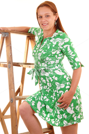 Girl in green dress. stock photo, Pretty young woman in an green dress standing on a stepladder, smiling in the canera, on white background. by Horst Petzold