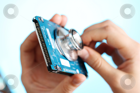 Doctor holding a stethoscope against a back side of the notebook HDD stock photo, Doctor holding a stethoscope in her fingers against a back side of the notebook harddisk by Andrey Yanevich