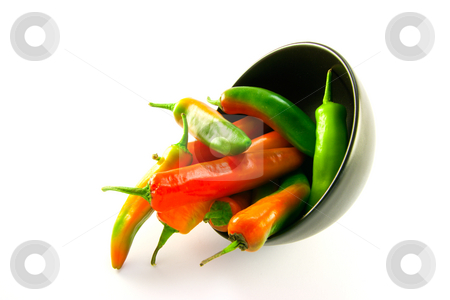 Chillis Spilling out of a Black Bowl stock photo, Mixed red and green chillis spilling out of a black bowl with clipping path on a white background by Keith Wilson
