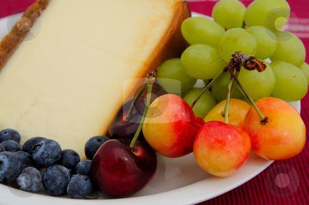Cheese Cake With Fresh Fruit stock photo, Seasonal fruit with a slice of plain cheese cake with a mint leaf garnish served on a white saucer. Blueberries, cherries and green seedless grapes. by Lynn Bendickson