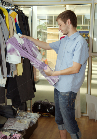 Showroom stock photo, The young man chooses to itself clothes in a supermarket. by Sergey Goruppa