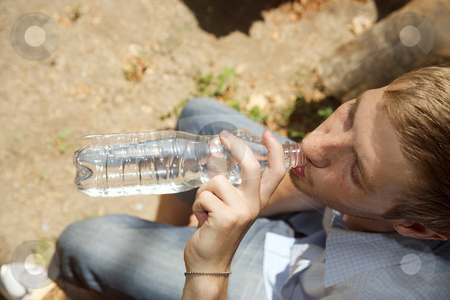 Thirst stock photo, The young guy drinks water from a bottle by Sergey Goruppa