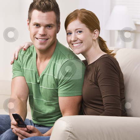 Attractive Couple Smiling with Cellphone stock photo, An attractive young couple sitting on a couch and smiling.  They are looking directly at the camera.  The male is holding a cell phone. Square composition. by Jonathan Ross