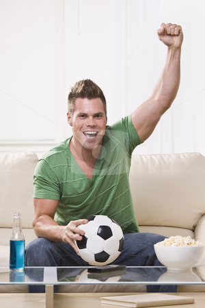 Soccer Fan Pumping His Fist While Watching the Game stock photo, An attractive young man holding a soccer ball and cheering with his fist in the air.  He is looking directly at the camera. Vertically framed photo. by Jonathan Ross