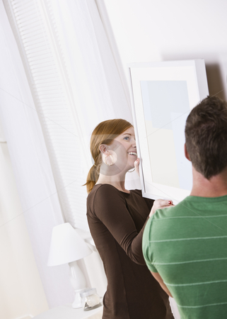 Young Couple Hanging Frame stock photo, A young couple hanging a picture frame together in their home.  Vertically framed shot. by Jonathan Ross