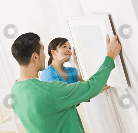 Asian couple hanging art stock photo, Asian woman and male hanging art on wall. Square composition. by Jonathan Ross