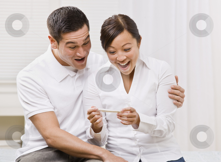 Ecstatic Couple Looking at a Pregnancy Test Together. stock photo, Attractive couple surprised and overjoyed reading pregnancy test. Square composition by Jonathan Ross