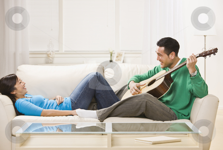 Asian couple on couch relaxing together. stock photo, Asian couple on couch playing guitar. Man serenading the woman. Horizontal by Jonathan Ross