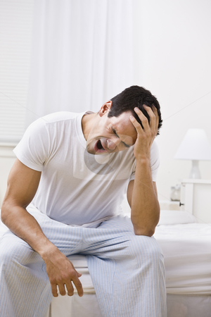 Attractive Man Yawning and Looking Sleepy stock photo, A man yawning.  He is sitting on the edge of a bed. Vertically framed shot. by Jonathan Ross