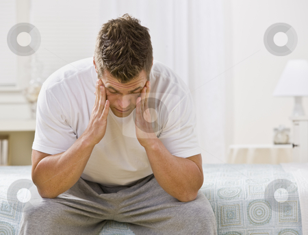 Young Man Sitting on Bed stock photo, A man is seated on the bed in a bedroom.  He has his head in his hands and is looking away from the camera.  Horizontally framed shot. by Jonathan Ross