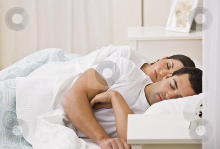 Couple Sleeping in Bed stock photo, An attractive young couple sleeping. They have their eyes closed. Horizontally framed shot. by Jonathan Ross