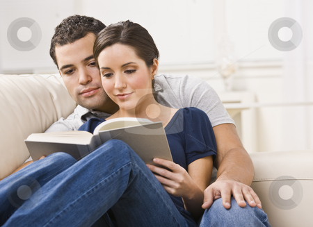 Cozy Couple Reading Book stock photo, A young, attractive couple is seated together on a couch and are reading a book together.  They are looking away from the camera.  Horizontally framed shot. by Jonathan Ross