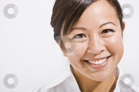 Beautiful Asian Woman Smiling stock photo, The headshot of a beautiful asian woman smiling.  She is isolated with a white background and is smiling at the camera.  Horizontally framed shot. by Jonathan Ross