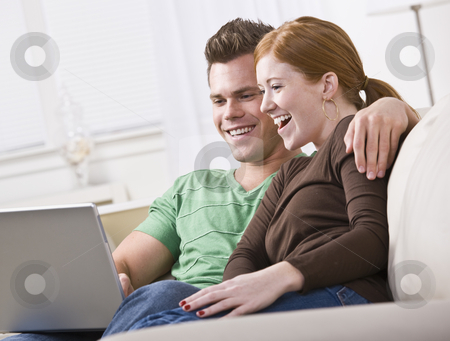 Couple Viewing Laptop stock photo, A young and attractive couple sitting together and viewing a laptop screen. They are smiling and laughing. Horizontally framed photo. by Jonathan Ross