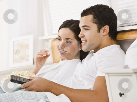 Couple Watching Television stock photo, An attractive young couple lying in bed and watching television.  They have a bowl of popcorn and a remote. They are smiling. Horizontally framed photo. by Jonathan Ross