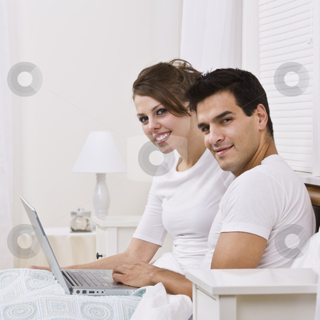Couple with Laptop stock photo, An attractive young couple sitting in bed together and holding a laptop.  They are smiling into the camera and are both wearing white. Square framed photo. by Jonathan Ross