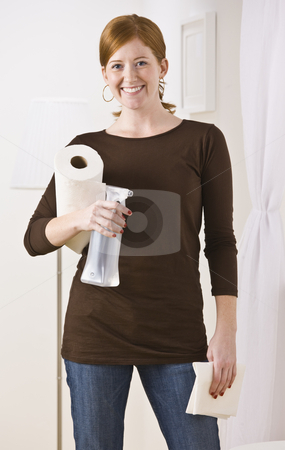 Woman With Cleaning Supplies stock photo, An attractive young woman holding cleaning supplies.  She is smiling directly at the camera. Vertically framed photo. by Jonathan Ross