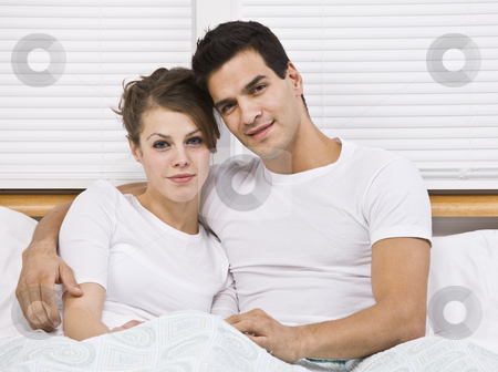 Attractive couple in bed together stock photo, Male and female attractive couple snuggling in bed, horizontally framed by Jonathan Ross
