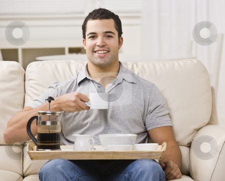Man with Breakfast Tray and Coffee stock photo, An attractive young man eating from a breakfast tray.  He has a coffee cup raised, and is smiling directly at the camera.  Horizontally framed photo. by Jonathan Ross