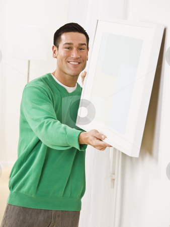 Cute man hanging canvas on Apartment Wall stock photo, Cute male trying to hang a blank canvas on the wall, vertically framed. by Jonathan Ross
