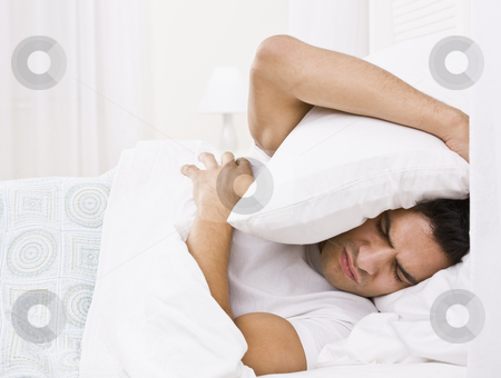 Tired Man Hiding His Head with Pillow stock photo, A tired looking man in bed.  He is holding a pillow over his head and is scowling. Horizontally framed shot. by Jonathan Ross