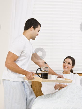 Man Serving Breakfast Tray to Woman stock photo, An attractive man serving breakfast on a tray to a beautiful woman in bed.  They are gazing at each other lovingly. Vertically framed shot. by Jonathan Ross
