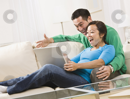 Couple Laughing While Looking at a Laptop Together stock photo, An attractive young couple sitting on a couch together and viewing laptop screen.  They are laughing. Horizontally framed shot. by Jonathan Ross