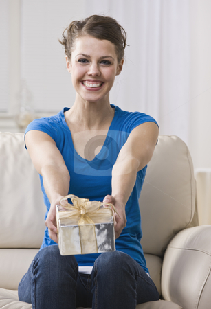 Woman Holding Up a Present to the Camera stock photo, An attractive young woman sitting on a couch and presenting a gift box.  She is smiling at the camera. Vertically framed photo. by Jonathan Ross