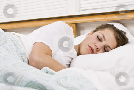 Beautiful Woman Sleeping stock photo, A beautiful young woman is sleeping in her bed.  Horizontally framed shot. by Jonathan Ross
