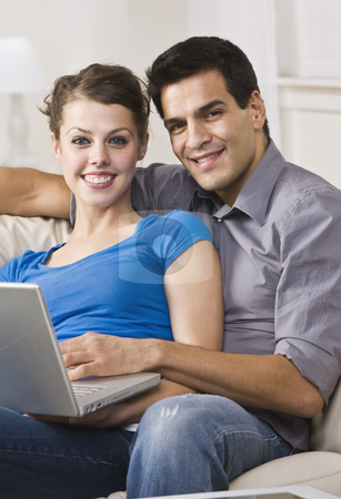 Happy Couple Using Laptop stock photo, An attractive and happy couple sitting together on a couch and using a laptop.  They are smiling directly at the camera.  Vertically framed shot. by Jonathan Ross