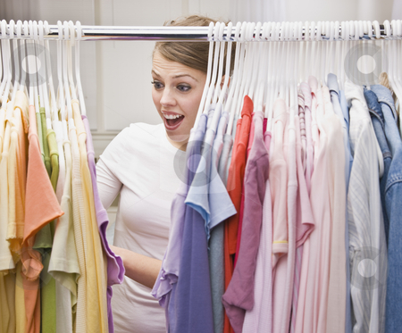 Woman in Closet stock photo, An attractive young female looking through clothing in a closet.  She has an excited expression on her face.  Vertically framed photo. by Jonathan Ross