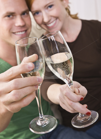 Attractive Young Couple Toasting stock photo, An attractive young couple toasting champagne flutes happily. They are smiling at the camera. Vertically framed shot. by Jonathan Ross