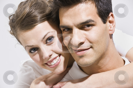 Close-up Couple stock photo, An up-close shot of a couple posing.  The female has her arms embraced around the male's neck.  They are smiling directly at the camera. Horizontally framed photo. by Jonathan Ross