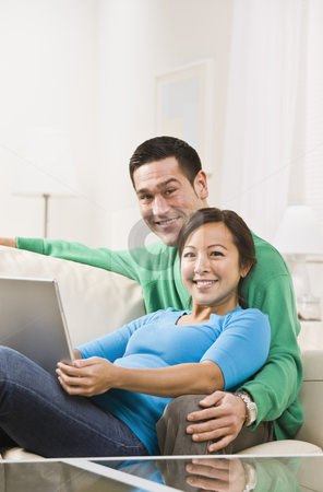 Couple Hugging with Laptop stock photo, An attractive young couple sitting on a couch together and holding a laptop.  They are smiling at the camera. Vertically framed shot. by Jonathan Ross