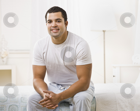 Happy Man Sitting on Bed stock photo, A happy looking man seated on a bed in a white room.  He is smiling and looking at the camera.  Horizontally framed shot. by Jonathan Ross