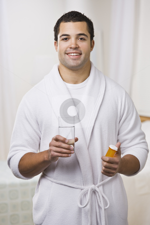 Man Taking Pills stock photo, An attractive young man holding a prescription bottle and glass of water.  He is wearing a bathrobe and is smiling at the camera. Vertically framed photo. by Jonathan Ross