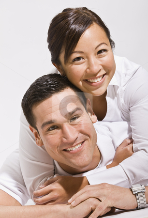 Asian couple hugging stock photo, Attractive asian couple hugging with woman on top.vertical by Jonathan Ross