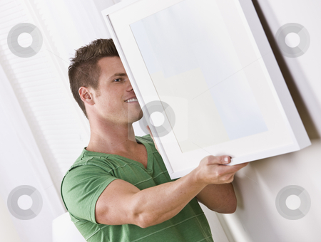 Man Hanging Frame stock photo, An attractive young man attempting to hang a picture frame.  Horizontally framed shot. by Jonathan Ross