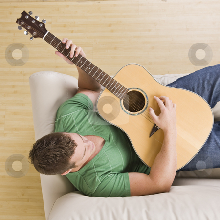 Man playing guitar on his couch. stock photo, Man laying on couch playing guitar. Top view, square composition. by Jonathan Ross