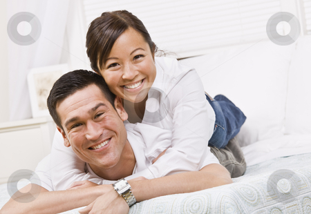 Happy Couple Posing on a Bed stock photo, A happy and attractive young couple posing together.  They are lying down and are smiling at the camera. Horizontally framed shot. by Jonathan Ross