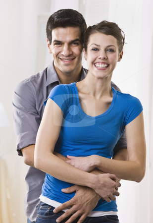 Cute couple embracing stock photo, Attractive Brunette couple standing in embrace. vertical by Jonathan Ross