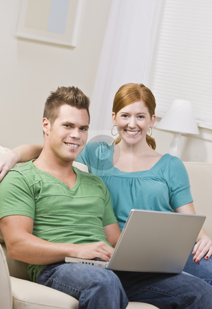 Happy Couple on Computer stock photo, A young, attractive couple is seated together on a couch and are working on a computer.  They are smiling at the camera.  Vertically framed shot. by Jonathan Ross
