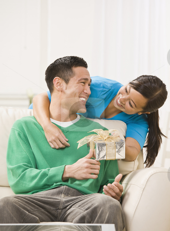Attractive Couple Exchanging Gifts stock photo, An attractive young exchanging a gift.  They are smiling directly at one another. Vertically framed photo. by Jonathan Ross