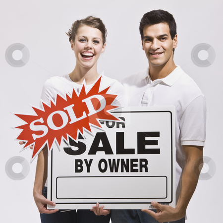Couple with For Sale by Owner Sign stock photo, An attractive young couple holding a real estate sign with a 'sold' sticker on it.  They are smiling directly at the camera and look excited. Square. by Jonathan Ross