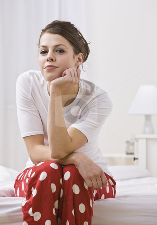Woman on Bed Wearing Red Polka Dot Pajamas stock photo, An attractive young woman sitting on the edge of a bed in her pajamas.  She is resting her chin on her hand and is smiling slightly toward the camera. Vertically framed photo. by Jonathan Ross